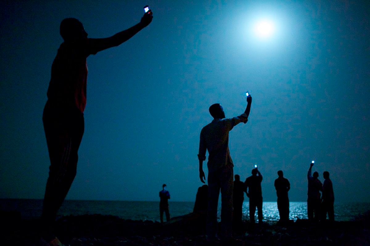 Afrikanische Migranten stehen bei Nacht an einem Strand in Dschibuti. Sie halten ihre Handys in die Höhe und hoffen darauf, ein Netz zu bekommen. Für eine Verbindung in die Heimat, die sie zurückgelassen haben. Somalia etwa, Äthiopien oder Eritrea.