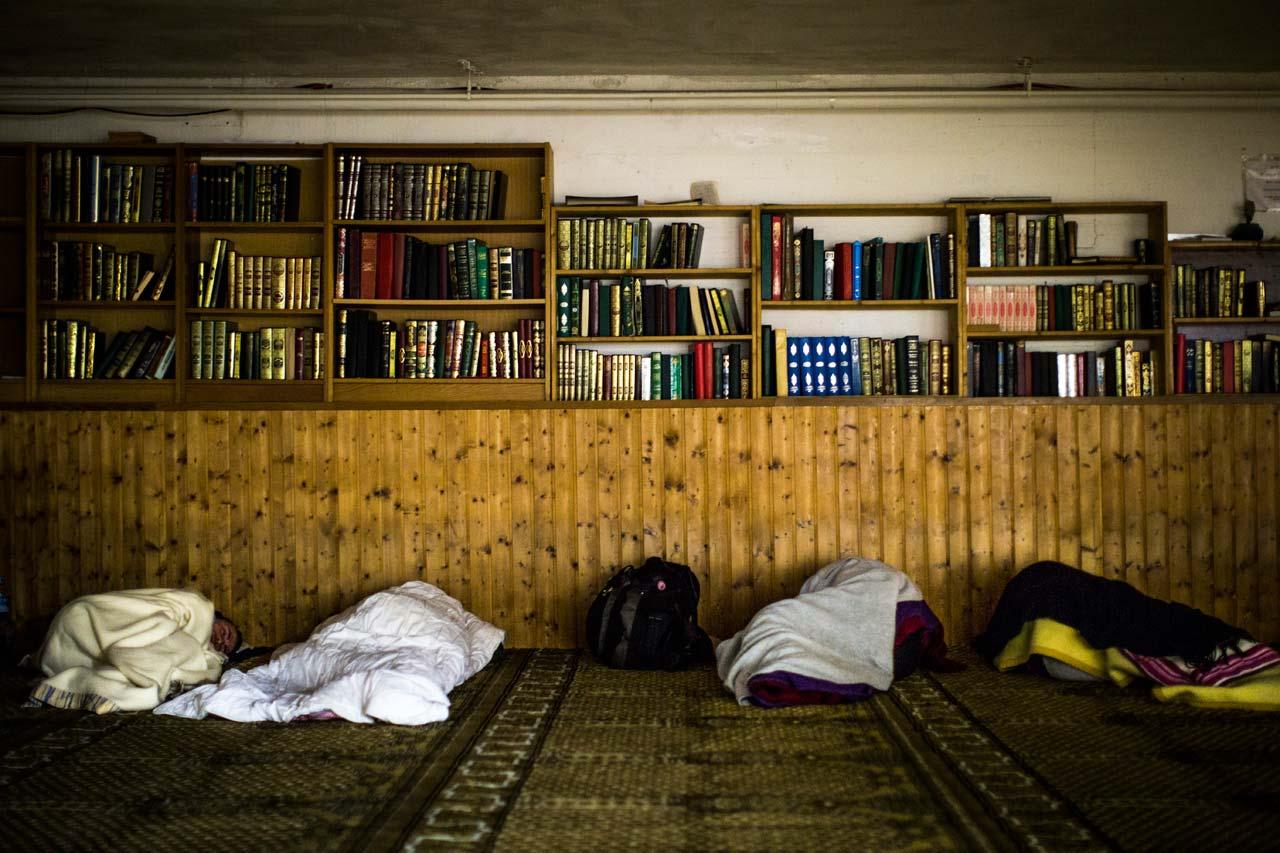 Der Gebetsraum der Al-Nour Moschee wird als Notunterkunft für die Nacht umgenutzt. Am Eingang bekommt jeder eine Decke und sucht sich dann einen Platz auf dem Gebetsteppich. Foto: Philipp Reiss