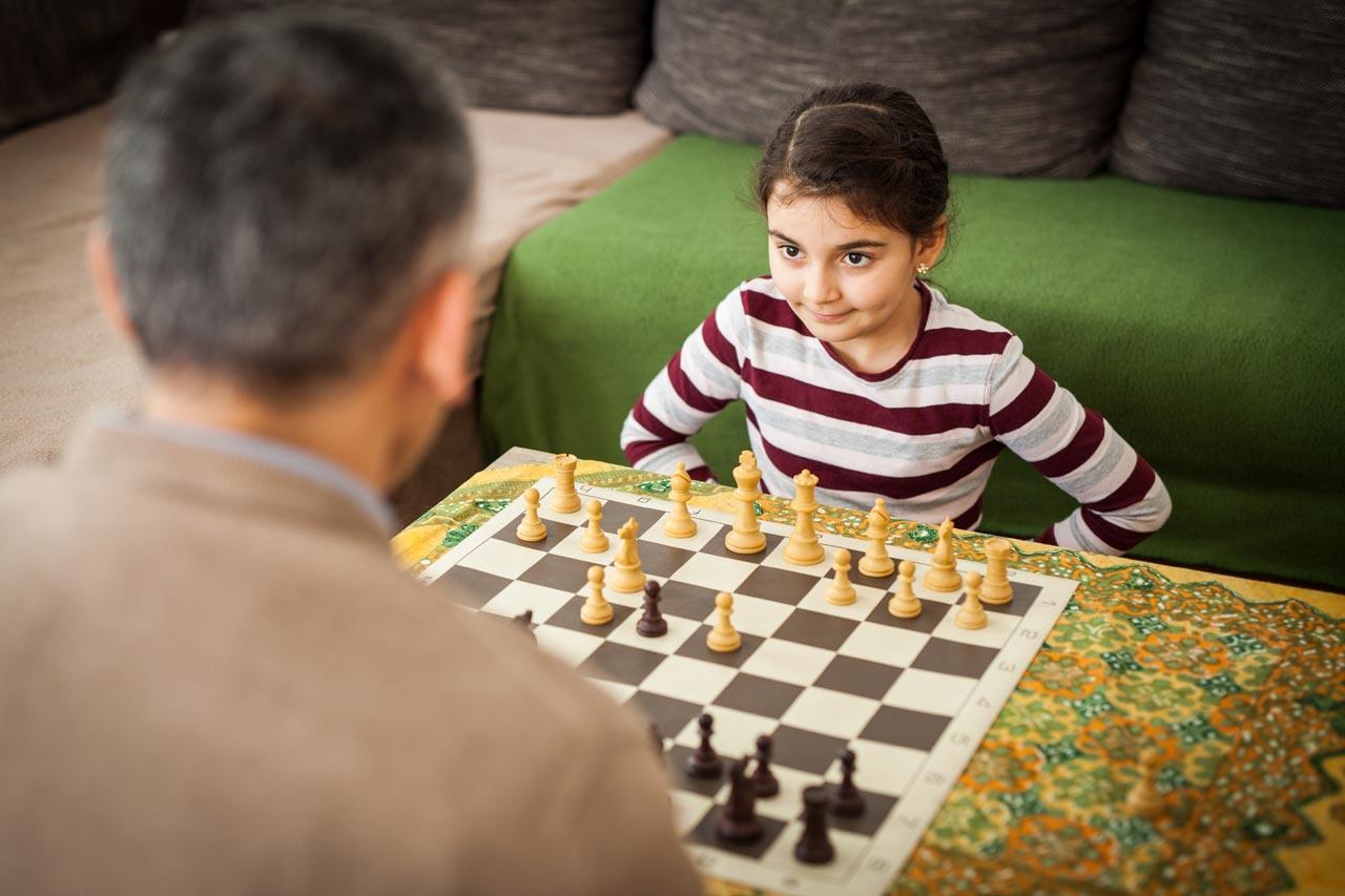 Lilian mit ihrem Vater Ayman beim Schach. Das Schachspielen stellt eine Abwechslung zum immer gleichen Alltag aus Schule, Lernen und Jobsuche dar. »Machmal schaue ich meinem Vater zu, wie er am Computer Schach spielt. Dabei lerne ich immer etwas«, erzählt die Tochter. Foto: Gesche Jäger