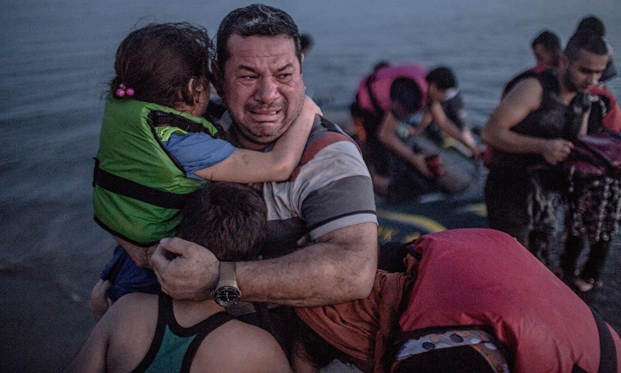 Angst und Sorgen fallen von dem irakischen Vater Laith Majid ab, als er mit seinen Kindern endlich an der rettenden Küste der griechischen Insel Kos angekommen ist, 15. August 2015. Foto: Daniel Etter