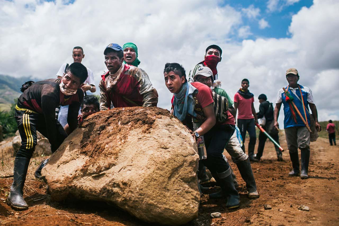 Im Südwesten Kolumbiens rollen Männer vom Volk der Nasa einen Stein auf die Straße, um Polizei und Militär den Zugang zu einer besetzten Zuckerrohrplantage zu versperren. Sie fordern Ackerland, das ihnen die Regierung versprochen, aber nie zugeteilt hat. Mit einer unbewaffneten Schutztruppe, der Guardia Indigena, kämpfen sie für ihr Recht. Foto: Jonas Wresch