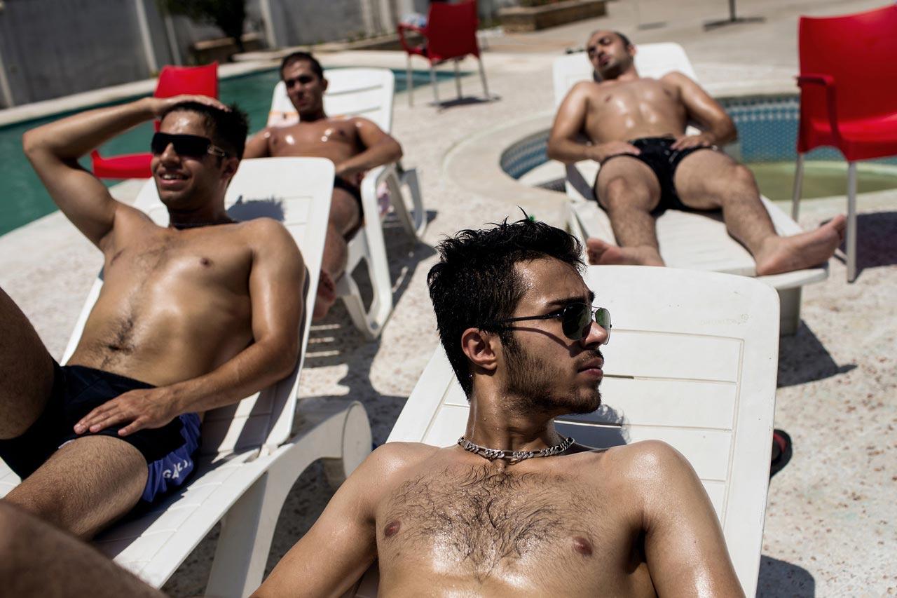 Junge Männer beim Sonnenbaden an einem Pool. Auch wenn im Nordiran die islamischen Regeln im Privaten oft locker ausgelegt werden; im Schwimmbad wird nach wie vor auf eine strenge Geschlechtertrennung geachtet.