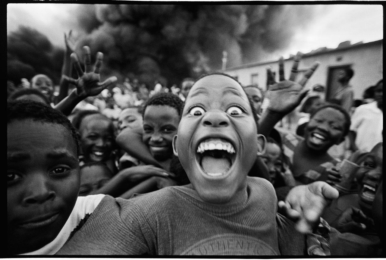 Ein immenser Brand von Autoreifen, wahrscheinlich ausgelöst durch Jugendliche. Voller Energie rast eine Gruppe von Kindern lachend auf den Fotografen zu. Erik Hinz macht in 5 Sekunden manuell 15 Bilder – dann ist die Situation auch schon wieder vorbei. Community Kanyamazane, Region Mpumalanga, Südafrika 1998. Foto: Erik Hinz
