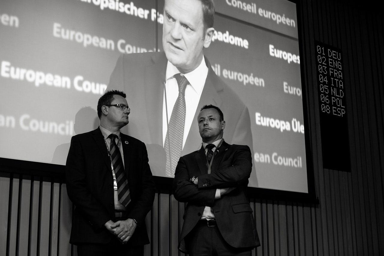 Sicherheitspersonal beim EU-Gipfeltreffen in Brüssel im Dezember 2015 vor einem Monitor, auf dem Donald Tusk, Präsident des europäischen Rates, während einer Ansprache zu sehen ist. Themen des Gipfels waren unter anderem die europäische Flüchtlingspolitik und der »Brexit«. Foto: Kaveh Rostamkhani