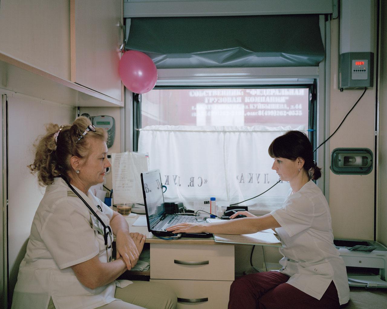 Allgemeinmedizinerin Ljudmila Michailowna Danilowa (l.) und ihre Assistentin werten in dem kleinen Behandlungsabteil Diagnosen aus. Sie sollen jeden Tag um die 37 Patienten behandeln. Foto: Emile Ducke