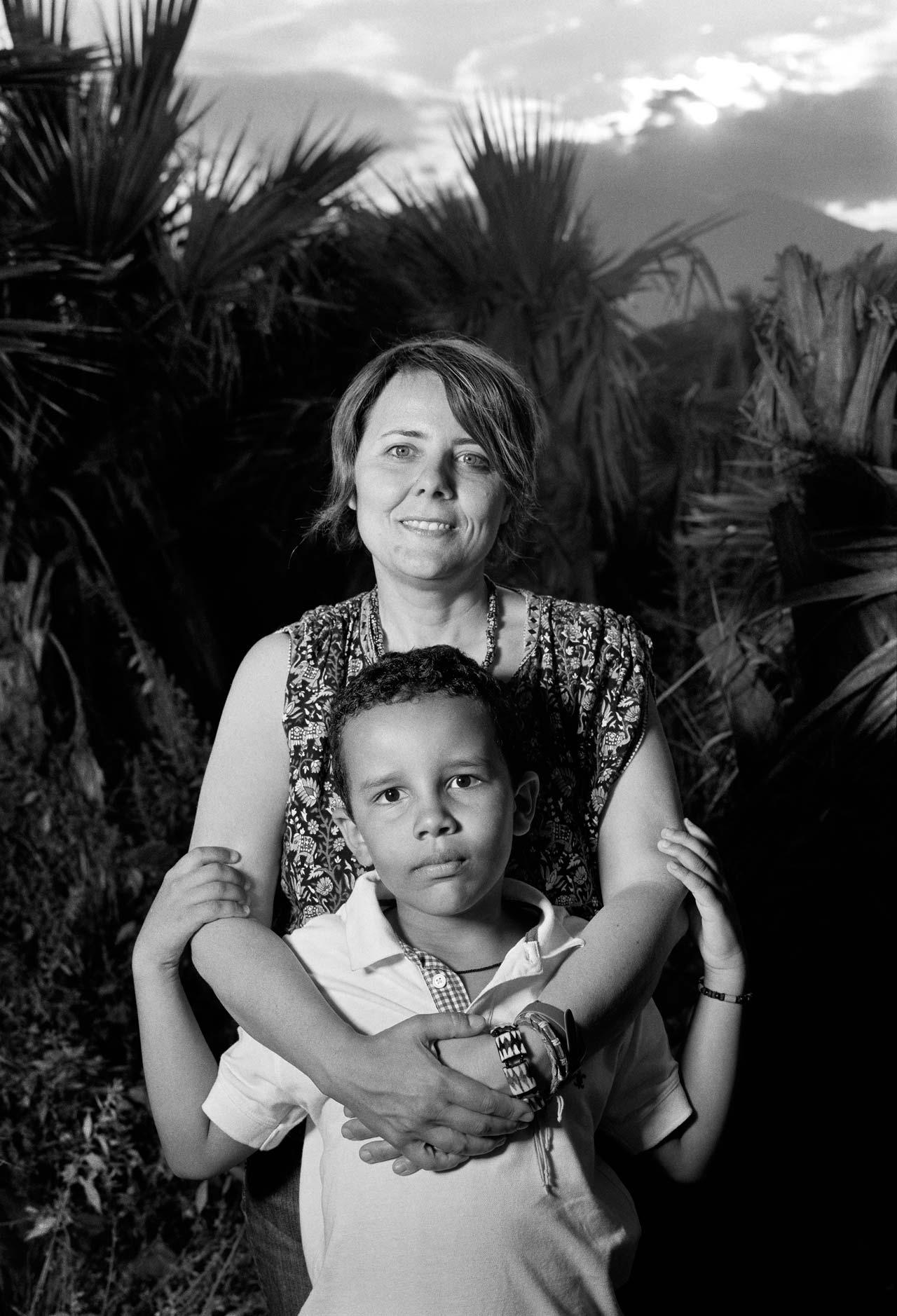 »Seit 10 Monaten habe ich keinen Lohn mehr bekommen. Am Schluss hatten wir nicht einmal mehr Geld für das Essen der Flüchtlinge. Ich frage mich, wohin das viele Geld der EU geflossen ist. Das Ganze ist ein riesiges Geschäft!« – Lella Pennisi, 42, die als Sozialarbeiterin für eine private Hilfsorganisation Geflüchtete aus Nordafrika betreute, mit ihrem Sohn Okada Buluma, 7, Acireale, Sizilien, Italien. Foto: Stefan Enders