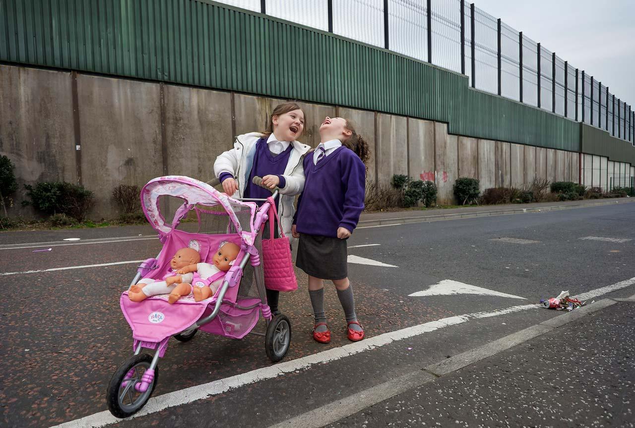 Noch immer trennt in West-Belfast eine Mauer die protestantischen von den katholischen Wohngebieten. Die beiden Mädchen haben ihre Schuluniformen noch nicht abgelegt, als sie ihre beiden Puppen auf der katholischen Seite spazierenfahren. Belfast, Nordirland. Foto: Stefan Enders