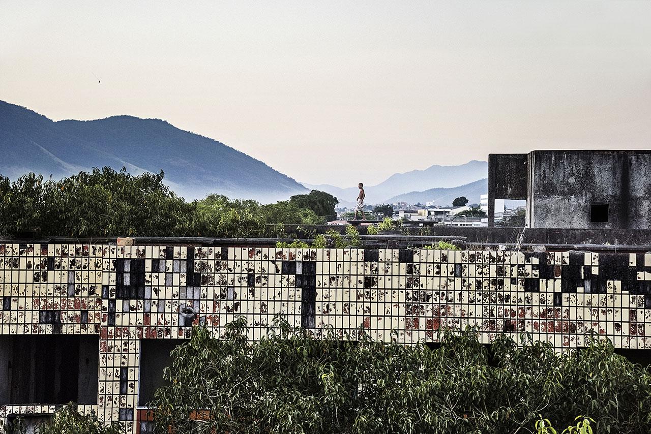 Ein Junge spielt auf dem Dach eines unfertigen Condos mit seinem Drachen. Alle sechs Gebäude wurden vor ca. 30 Jahren für die Mittelschicht gebaut. Die finanzielle Krise der Baufirma stoppte das Megaprojekt jedoch und die Hausbesetzung ließ nicht lange auf sich warten. Foto: Peter Bauza