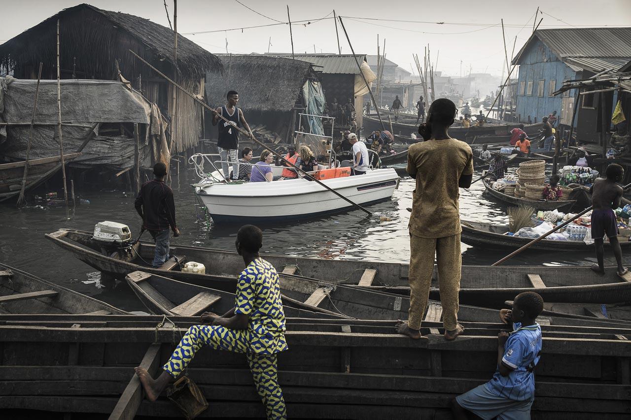 »Lagos Waterfronts under Threat«. Ein Boot bringt Touristen von der Marina in Lagos, Nigeria zu den Kanälen Makokos, einem ehemaligen Fischerdorf, das zu einer riesigen informellen Siedlung angewachsen ist. Foto: Jesco Denzel/laif