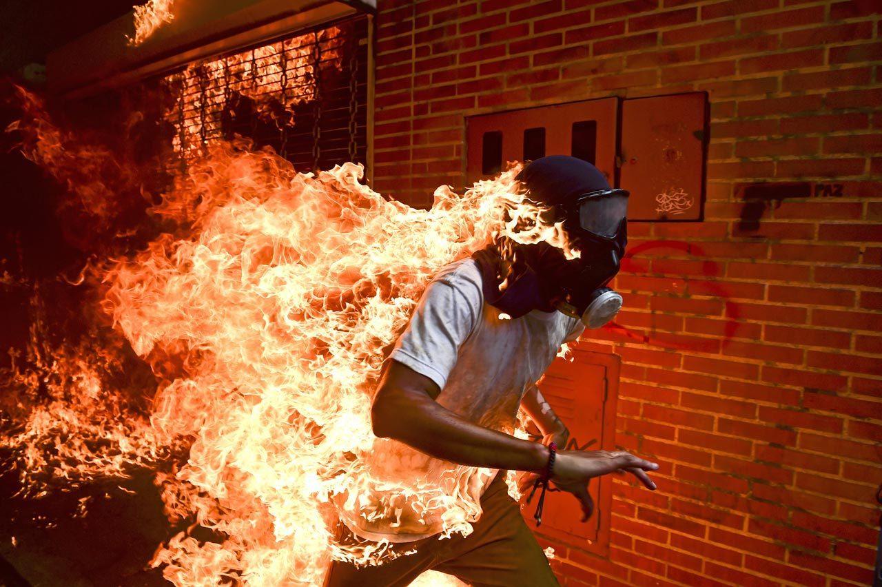 »Venezuela Crisis« hat Fotograf Ronaldo Schemidt sein Bild von José Víctor Salazar Balza (28) betitelt, der in Caracas während einer Demonstration gegen Präsident Nicolas Maduro bei Auseinandersetzungen mit der Polizei Feuer gefangen hat. Foto: Ronaldo Schemidt/Agence France-Presse